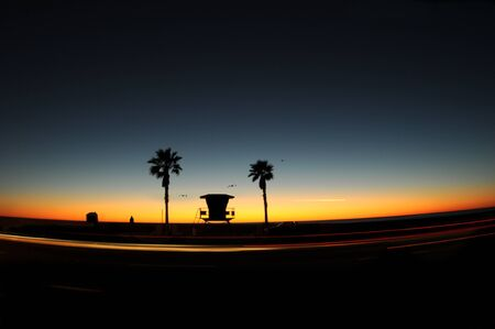 Silhouette of lifeguard tower at sunset, birds and airplane in the sky  and car lights in motion.