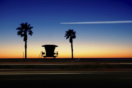 석양 야자수와 근 위 기병 연대 타워입니다. 오렌지, 블루 스카이와 자동차 모션에 걸쳐 비행 비행기. 스톡 콘텐츠