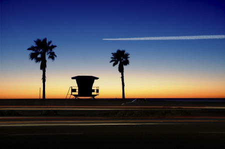 across: Lifeguard Tower with Palm trees at sunset. Airplane flying across the orange, blue sky and cars in motion. Stock Photo