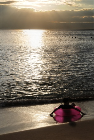 Kid relaxing at the beach on a pink buoy watching the sunset. Maui, Hawaii. Stock Photo
