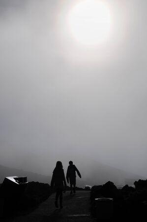 Two kids walking the trail on a foggy day at Haleakala  National Park. Maui, Hawaii.