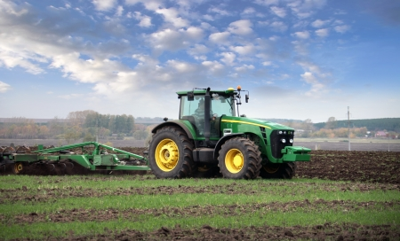 machinery space: agricultural work plowing land on a powerful tractor Stock Photo