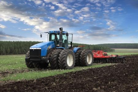 強力なトラクターの土地を耕し農作業