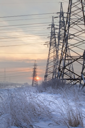 An unusual view of the high voltage on a snowy meadow photo