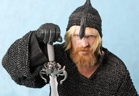 close-up portrait of a warrior man with a beard and mustache, sword in chain mail and a helmet with a light background