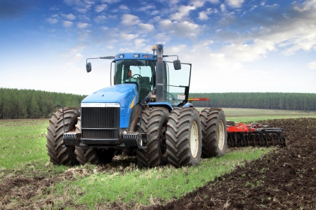 farm tractor: agricultural work plowing land on a powerful tractor Stock Photo