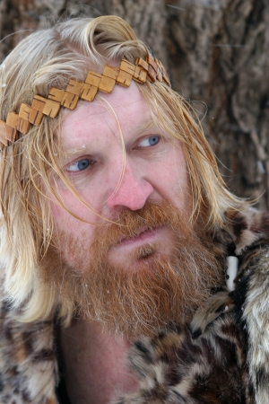 close-up portrait of a man with a red beard and mustache, blond hair, wearing a fur clothing, bandage on his head, , looking to the side Banque d'images