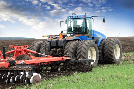 agriculture industry: agricultural work plowing land on a powerful tractor Stock Photo