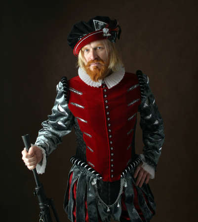 close-up portrait of a man of the Middle Ages with a beard and mustache in a suit isolated on a dark background with a weapon Stock Photo