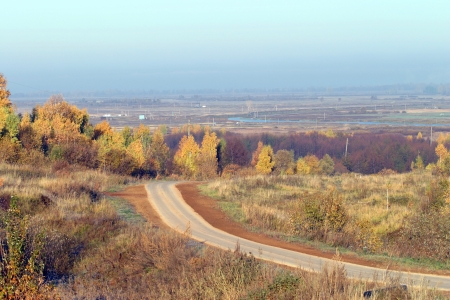 autumn landscape, the road receding into the distance beyond the horizon in the Russian fields photo