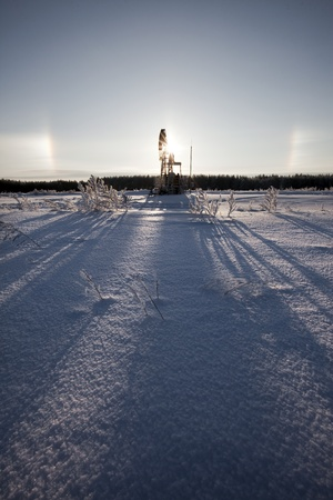 Oil pitching winter day on the background of the solar halo
