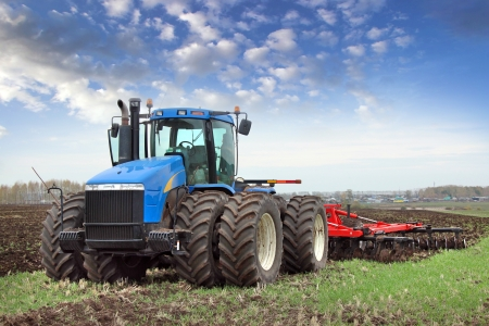 farm equipment: agricultural work plowing land on a powerful tractor Stock Photo