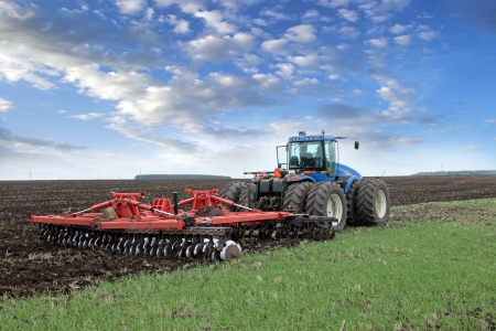 agriculture machinery: agricultural work plowing land on a powerful tractor Stock Photo