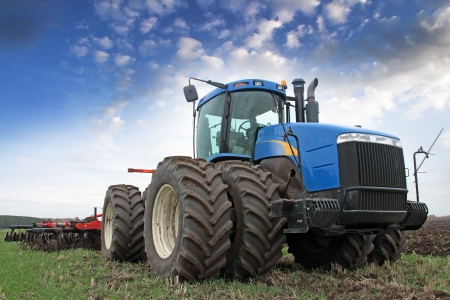 wheel tractor: agricultural work plowing land on a powerful tractor Stock Photo