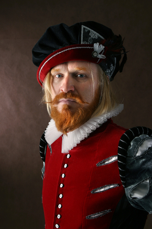 bard: close-up portrait of a man of the Middle Ages with a beard and mustache in a suit isolated on a dark background Stock Photo