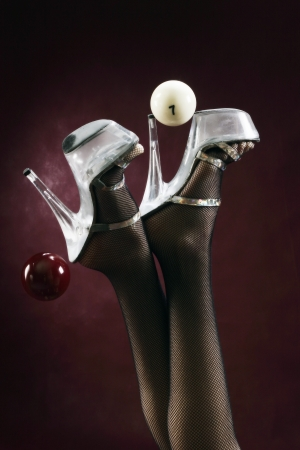 close-up of female legs in stockings and shoes and billiard balls studio Stock Photo