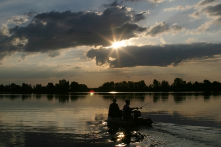 Two men go fishing from a boat on the river at sunset in late summer photo