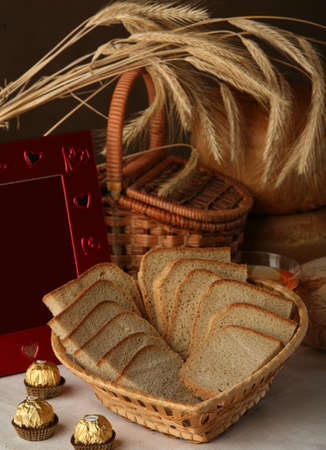 edibles: close-up of sliced brown bread in wicker basket and other edibles studio on a brown background Stock Photo