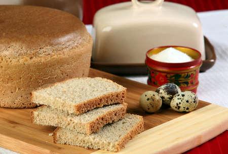 edibles: close-up di pane a fette su un tagliere e di altri commestibili in studio