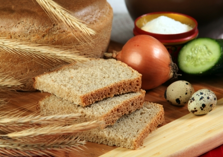 close-up of sliced bread on a cutting board and other edibles studio photo