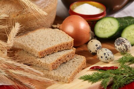 edibles: close-up of sliced bread on a cutting board and other edibles studio