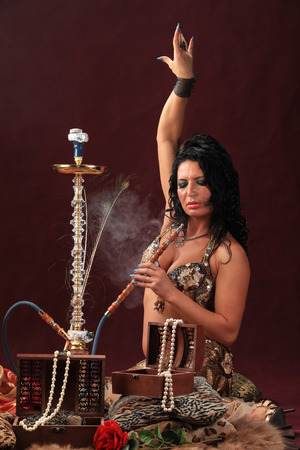 portrait of oriental girl sitting on the floor smoking a hookah vertical location, studio on burgundy background