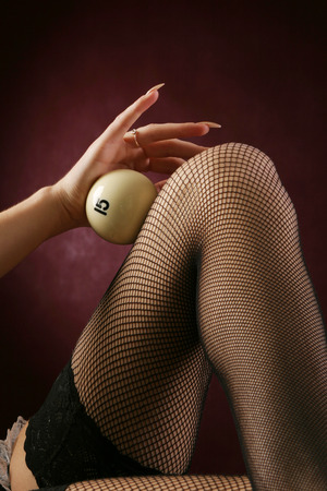 close-up on a womans knee in a stocking clad ivory billiard ball on a burgundy background studio photo