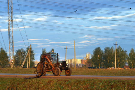 landscape tractor driving on a road at sunset in summer photo