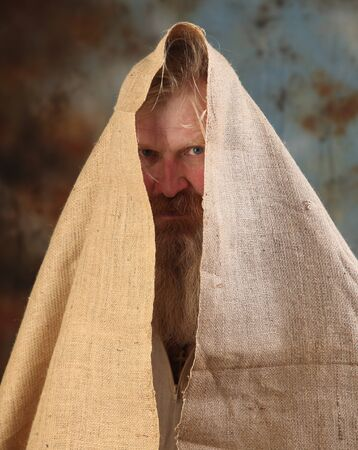 Portrait old beggar with a beard and mustache, wrapped in burlap, with pain and despair in his eyes, the studio on a brown-blue background Stock Photo