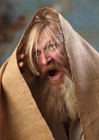 humilde: Retrato viejo mendigo con una barba y bigote, envuelto en arpillera, con dolor y desesperación en sus ojos, el estudio sobre un fondo marrón-azul Foto de archivo