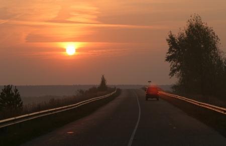 autumn landscape asphalt road on a foggy evening sunset photo