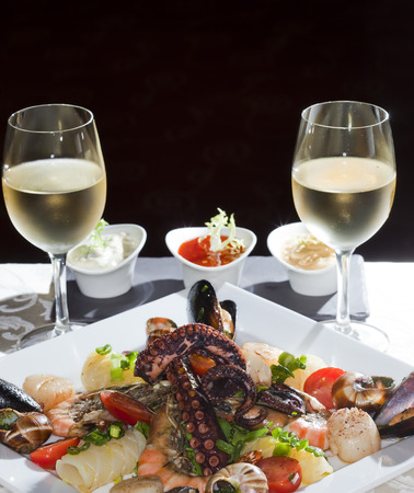 Macro still life white dish with seafood and wine glasses with white wine on a white tablecloth in a studio on a black  photo