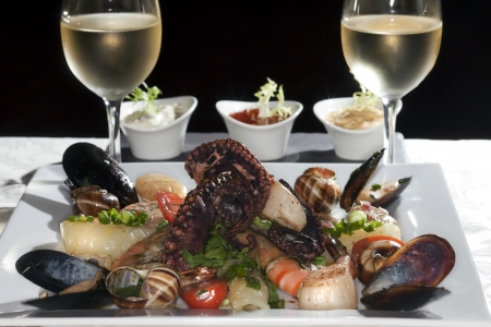 Macro still life white dish with seafood and wine glasses with white wine on a white tablecloth in a studio on a black background Stock Photo