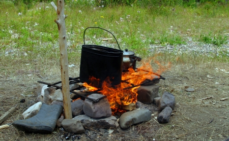 isolated close-up sooty pot and kettle on a fire during a summer hike photo
