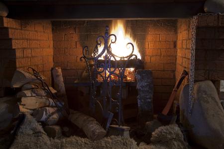 Close-up van bakstenen open haard met een ijzeren poort met een heldere vlam brandende logs