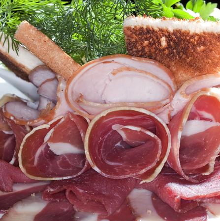 fiambres: Primer plano de una variedad de carnes con hierbas y tostadas tostadas en el plato blanco estudio aislado en negro Foto de archivo