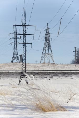 winter landscape power lines in a snowy field near the forest photo