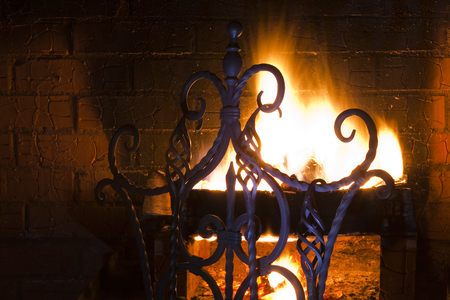 whiff: close up of a beautiful wrought-iron grate against the bright flame and a brick wall Stock Photo