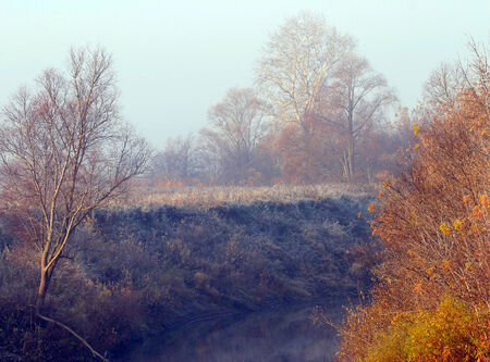 Autumn landscape dense fog over the river and hoarfrost on trees and grass photo