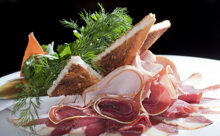 cold cuts: Close-up of assorted meats with herbs and toasted toasts on white dish isolated studio on black background