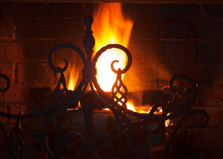 close up of a beautiful wrought-iron grate against the bright flame and a brick wall photo