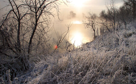 Winter landscape frosty misty morning on the river and trees in hoarfrost Stock Photo