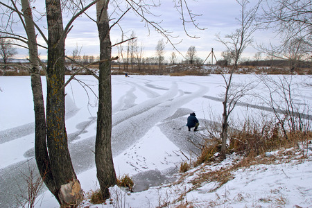 Winter landscape fishermen catch fish in the river covered with ice at the beginning of the winter at sunrise photo