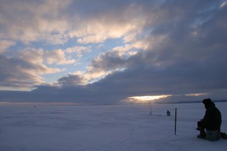 winter landscape fisherman fishing on the estuary Eek river at sunset photo