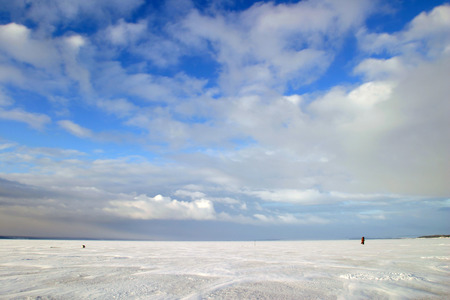 amazing winter landscape beneath the ice of a broad river and beautiful clouds in the blue sky photo