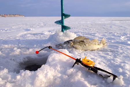 close-up boer, hengel en vissen rond het ijs-gat op de rivier de winter in een zonnige dag Stockfoto