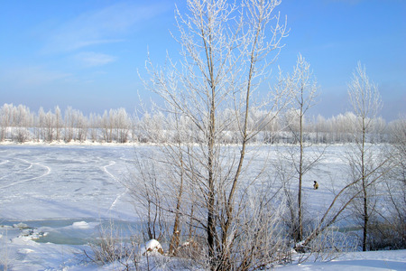 Scenic winter landscape beneath the ice reservoir wonderful blue sky fog and frost on the trees on the shore photo