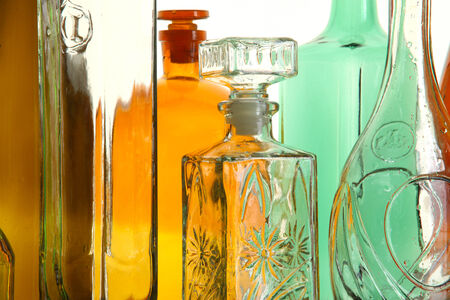 different shapes: close-up clean transparent colored glass bottles of different shapes on the mirror surface in white light studio