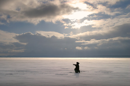 winter landscape fisherman fishing on the estuary Eek river at sunset photo