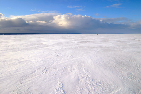 amazing winter landscape beneath the ice of a broad river and beautiful clouds in the blue sky